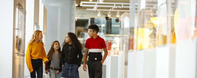 Group of kids of various ages walking in the Contemporary glass gallery with white cases