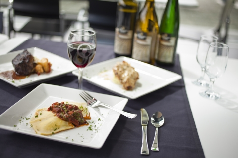 White plates with catered meal options: ravioli, chicken or steak with a variety of wines