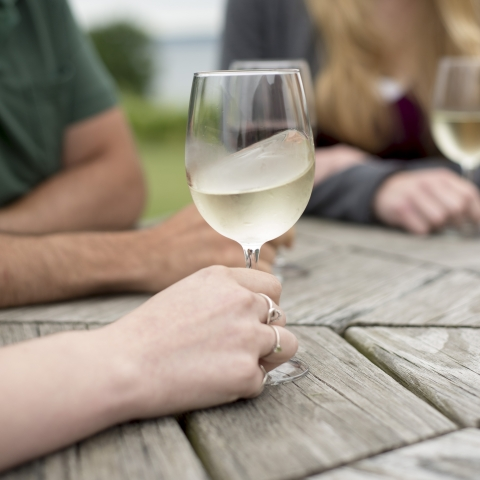 White wine swirling in a wine glass with three adults in the background