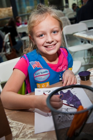 Young Girl Scout in blue vest colors with a purple marker