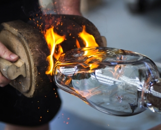 A gaffer rubs a clear glass oval sculpture with pads, creating flames