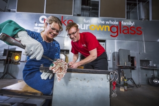 A woman wearing safety gear pulls a hot glass flower with the assistance of a man in a red tshirt