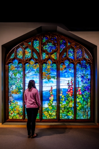 Guest standing in front of stained glass window scene of flowers and a lake