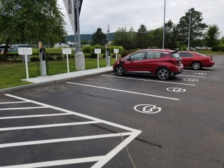 Two red cars using the recharging station in a parking lot