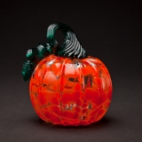 An orange blown glass pumpkin with a curly green stem