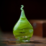 Green and clear glass sculpted in a teardrop-like shape with a twist at the top