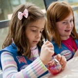 Two Girl Scouts in blue vests decorate clear glass ornaments with paint