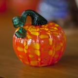 A glass pumpkin that is orange and yellow with a  green stem