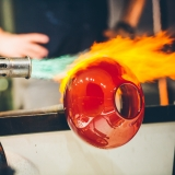 Close-up of a glassblower using flame to heat a red sphere