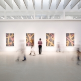 A guest looks at four glass works that are yellow and gray, while other guests are blurred as they move around the exhibit