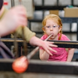 Child blowing into a pipe to create a sphere of molten glass
