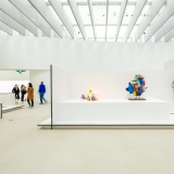 Wide shot of a white walled gallery with colorful glass sculptures and people in the distance in the far left
