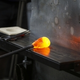A gob of hot glass is rolled on a marver