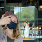 A guest wearing a black mask takes a selfie with a glass black and white penguin in a clear box in the background
