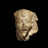 A tan sculpture of an Ancient Egyptian pharaoh's head on a black background