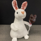 A glass sculpture of a white rabbit with pink ears, holding a rabbit-head shaped balloon in its right paw