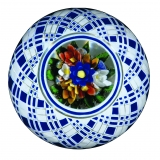 A glass paperweight with blue, red, yellow, and white flowers surrounded by blue and white checkered pattern