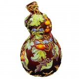 A brown glass gourd decorated with leaves, pumpkins, and dragonflies