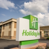 Green and white Holiday Inn sign, with the two-story tan hotel in the background