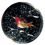 A glass paperweight of a red, white, and brown bird on a snow-covered branch, with snow in the background