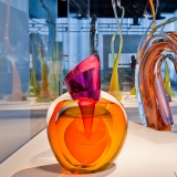 Three orange, pink, and clear glass objects of abstract shapes sit in a display case.