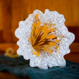 A glass flower with white petals and an orange center