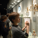Children look at glass objects in a glass case and complete a worksheet